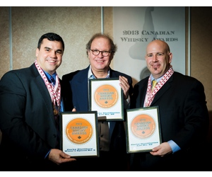 (Left) David Weaver and (right) Bill Atwood of Corby Distillers accept their award for Corby's Lot No. 40 from Davin de Kergommeaux at the Canadian Whisky Awards.