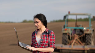 Young happy farmer girl standing on field with laptop in spring time. Tractor working in background