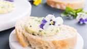 Sandwich with herb and edible flowers butter on marble cutting board. Healthy food.
