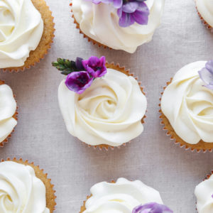 Rose flower frosting vanilla cupcakes with purple edible flowers