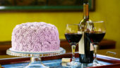 Deluxe 6 layer round chocolate butter cream cake with purple frosting and elegant glass stand